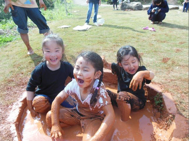 泥染めののための泥に入って遊ぶ子どもたち